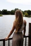 Blondes kaukasisches jugendlich Mädchen, das an der Schiene betrachtet Fluss steht Lizenzfreies Stockbild