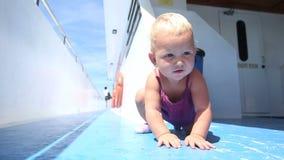 Blondes Kind, das auf einer blauen Schiffsplattform sitzt stock footage