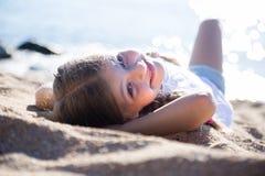 Blondes Kind, das auf sandigem Strand der Seeküste liegt Stockfotos