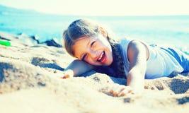 Blondes Kind, das auf sandigem Strand der Seeküste liegt Lizenzfreie Stockfotos