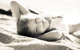 Blondes Kind, das auf sandigem Strand der Seeküste liegt Lizenzfreie Stockfotografie