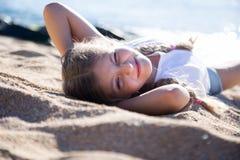 Blondes Kind, das auf sandigem Strand der Seeküste liegt Stockfotografie