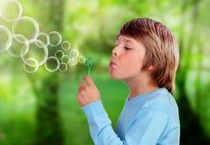 Blondes Kind, das Blasen durchbrennt und tut Stockbilder