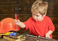 Blondes Kind, das in der Werkstatt spielt Jungenstellschrauben zum hölzernen Brett Starkes Kind, das neue Fähigkeiten lernt Lizenzfreie Stockfotos