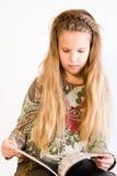 Blondes Kind, das ein Buch liest Stockfoto