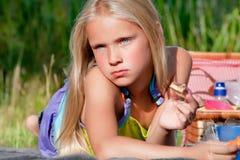 Blondes Kind, das ihre Nahrung genießt Stockfotos