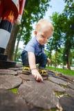 Blondes Kind, das im Frühjahr im Park sitzt Stockfotos