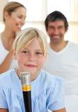 Blondes Kind, das mit einem Mikrofon singt Lizenzfreies Stockfoto