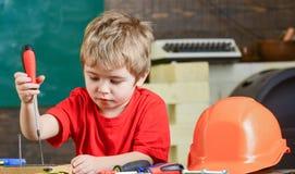 Blondes Kind der Nahaufnahme in der Werkstatt Jungenstellschrauben zum hölzernen Brett Starkes Kind, das neue Fähigkeiten lernt Lizenzfreie Stockfotos