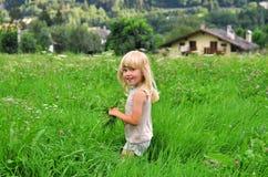 Blondes Kind in der Rasenfläche Stockfotografie