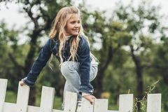 blondes Kind des Frühlinges, das über dem Zaun klettert Lizenzfreie Stockfotos