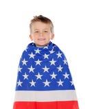 Blondes Kind eingewickelt auf amerikanischer Flagge Stockfotografie