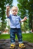Blondes Kind geht in den Park im Sommer Stockbild