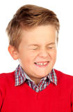 Blondes Kind mit einem lustigen Ausdruck, der seine Augen schließt Stockfoto