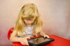 Blondes Kind mit Tablette Lizenzfreie Stockbilder