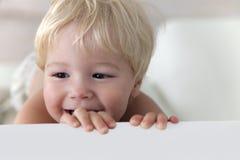 Blondes Kind schaut verschlagen von der Tabelle Lizenzfreie Stockfotos