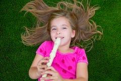 Blondes Kinderkindermädchen, welches die Flöte liegt auf Gras spielt Stockbild