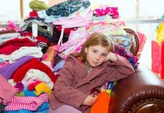 Blondes Kindermädchen, das auf einem unordentlichen Kleidungssofa sitzt Stockfoto