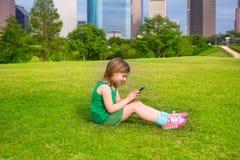 Blondes Kindermädchen, das mit dem Smartphone sitzt auf Parkrasen an c spielt Lizenzfreies Stockfoto