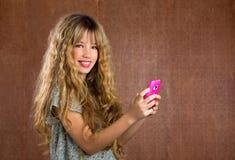 Blondes Kindermädchen, das mit Handyweinleseporträt spielt stockbilder