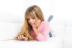 Blondes Kindermädchen, das mit Tabletten-PC auf weißem Sofa spielt stockbilder