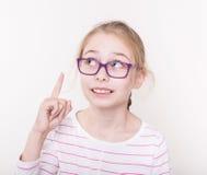 Blondes Kindermädchen in den violetten Gläsern Finger oben zeigend Lizenzfreie Stockfotografie