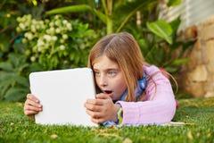 Blondes Kindermädchen mit dem Tabletten-PC, der auf Grasrasen liegt Stockfotos