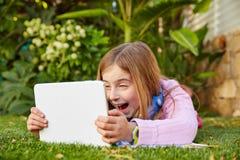 Blondes Kindermädchen mit dem Tabletten-PC, der auf Grasrasen liegt Lizenzfreie Stockfotos