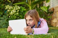 Blondes Kindermädchen mit dem Tabletten-PC, der auf Grasrasen liegt Stockfotografie