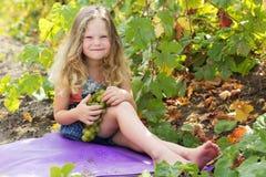 Blondes Kindermädchen mit Trauben burries im Weinberg Lizenzfreie Stockfotos