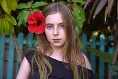 Blondes Kindermädchenporträt mit roter Blume Stockbild