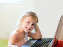 Blondes Kindmädchen, das mit Laptop lächelt Stockfotos