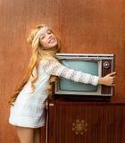 Blondes Kindmädchen der Weinlese 70s mit altem Fernsehapparat der Retro- Liebe Stockbilder