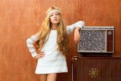 Blondes Kindmädchen der Weinlese 70s mit Retro- Holzfernsehapparat Stockfotos