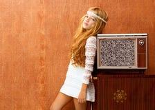 Blondes Kindmädchen der Weinlese 70s mit Retro- Holzfernsehapparat Stockfoto