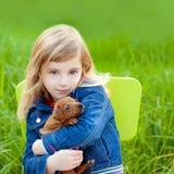Blondes Kindmädchen mit Welpenhaustierhund im grünen Gras Lizenzfreie Stockfotografie