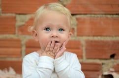 Blondes kleines Baby, das mit Freude schaut Stockfotos