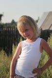 Blondes kleines Kindermädchen, das in der Landschaft, Sommerdorf aufwirft Lizenzfreie Stockfotos