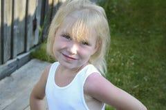 Blondes kleines Kindermädchen, das in der Landschaft, Sommerdorf aufwirft Lizenzfreie Stockbilder