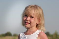 Blondes kleines Kindermädchen, das in der Landschaft, Sommerdorf aufwirft Lizenzfreies Stockfoto