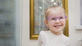 Blondes kleines Mädchen, beim Glaslächeln und Spiele in der Augenheilkundeklinik Stockfoto