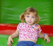 Blondes kleines Mädchen, das auf buntem Spielplatz stillsteht Lizenzfreie Stockfotografie