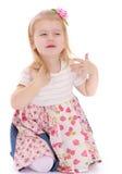 Blondes kleines Mädchen, das auf dem Boden sitzt Lizenzfreie Stockbilder