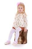 Blondes kleines Mädchen, das auf einem Birkenstumpf sitzt Lizenzfreie Stockfotos