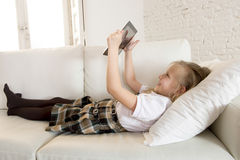 Blondes kleines Mädchen, das auf Hauptsofacouch unter Verwendung Internet-APP auf digitaler Tablettenauflage auf digitaler Tablet Stockbilder