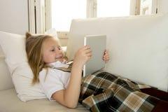 Blondes kleines Mädchen, das auf Hauptsofacouch unter Verwendung Internet-APP auf digitaler Tablettenauflage auf digitaler Tablet Lizenzfreie Stockfotografie