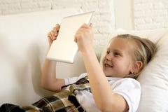 Blondes kleines Mädchen, das auf Hauptsofacouch unter Verwendung Internet-APP auf digitaler Tablettenauflage auf digitaler Tablet Lizenzfreie Stockfotos