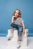 Blondes kleines Mädchen, das auf weißen Kästen sitzt und Kamera betrachtet Stockfoto