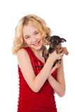 Blondes kleines Mädchen, das den Welpen trägt rotes Kleid hält Lizenzfreies Stockfoto