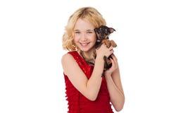 Blondes kleines Mädchen, das den Welpen trägt rotes Kleid hält Lizenzfreie Stockfotografie